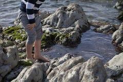 Garçon jouant et explorant dans les piscines de marée près de l'océan Photos stock