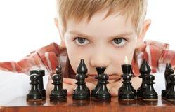 Garçon jouant haut proche d'échecs images stock