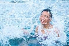 Garçon jouant l'eau éclaboussant sur la plage Photo stock