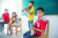 Garçon jouant l'ukulélé avec des amis dans la salle de classe de musique Photographie stock