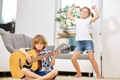 Garçon jouant la guitare et la fille dansant à la maison Photographie stock