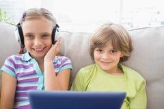 Garçon jouant la musique sur l'ordinateur portable pour la soeur dans le salon Photographie stock libre de droits