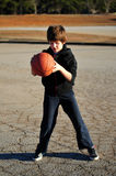 Garçon jouant le basket-ball sur un terrain de jeu Photos stock