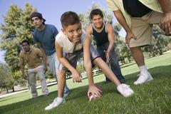 Garçon jouant le football américain avec le groupe des hommes Image libre de droits