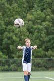 Garçon jouant le football - prenant un jet dedans photos stock