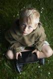 Garçon jouant le jeu avec le PC de comprimé dehors Photographie stock