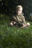 Garçon jouant le jeu avec le PC de comprimé dehors Images stock