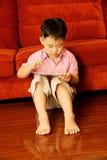 Garçon jouant le jeu sur la tablette attentivement Photo stock