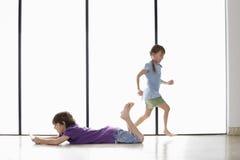 Garçon jouant le jeu vidéo tenu dans la main tandis que soeur Running Around photographie stock