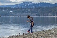 Garçon jouant le long de la plage photos stock