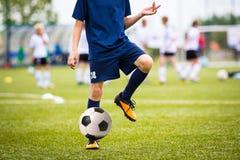 Garçon jouant le match de football du football sur un stade de sports Image stock