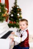 Garçon jouant le piano la veille de Noël Images libres de droits