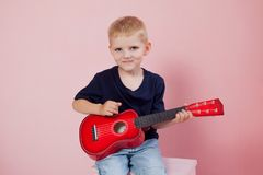 Garçon jouant le portrait de guitare sur un fond rose Photo libre de droits