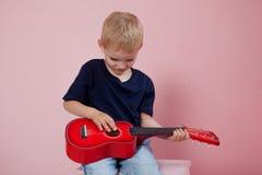 Garçon jouant le portrait de guitare sur un fond rose Image libre de droits