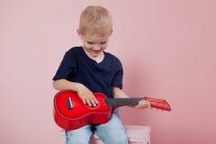 Garçon jouant le portrait de guitare sur un fond rose Photos stock