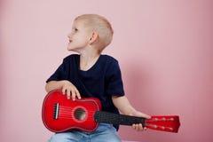 Garçon jouant le portrait de guitare sur un fond rose Photographie stock libre de droits