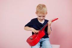 Garçon jouant le portrait de guitare sur un fond rose Image stock