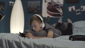 Garçon jouant le smartphone sur le lit banque de vidéos