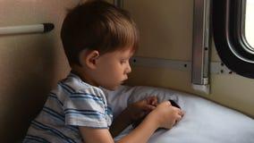 Garçon jouant les jeux mobiles dans le train clips vidéos