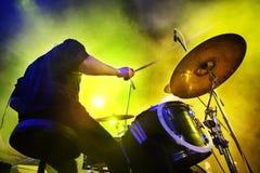 Garçon jouant les tambours. Lumières vivantes de concert et d'étape. Photos stock