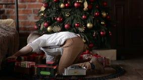 Garçon jouant près de l'arbre de Noël banque de vidéos