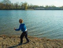 Garçon jouant près du lac Photographie stock libre de droits