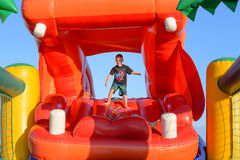 Garçon jouant sur l'hippopotame gonflable rouge géant Image stock