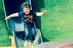 Garçon jouant sur la glissière Image libre de droits