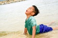 Garçon jouant sur la plage sous le ciel ensoleillé Photographie stock libre de droits