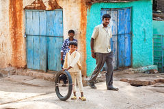 Garçon jouant sur la rue étroite avec les personnes de précipitation et les maisons rustiques Photographie stock libre de droits