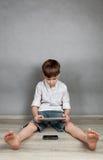 Garçon jouant sur le comprimé Image libre de droits