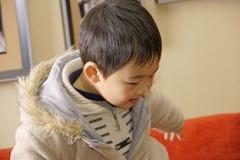Garçon jouant sur le divan Photo stock