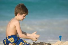 Garçon jouant sur une plage images stock