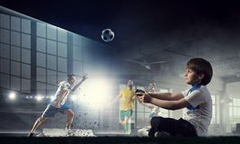 Garçon jouant un jeu vidéo Media mélangé Photographie stock