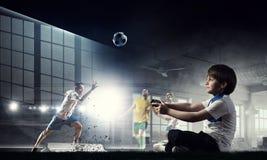 Garçon jouant un jeu vidéo Media mélangé Photo stock