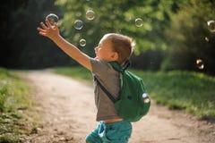 Garçon joyeux jouant avec des bulles de savon en parc d'été le jour ensoleillé images stock