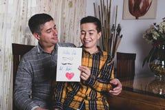 Garçon lisant la carte de félicitations pour engendrer le jour de père image libre de droits
