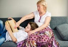 Garçon lisant un livre avec sa grand-mère d'intérieur Photographie stock libre de droits