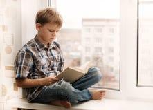 Garçon lisant un livre se reposant sur le rebord de fenêtre Photographie stock libre de droits