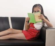 Garçon lisant un livre sur le furn image libre de droits
