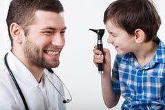 Garçon lors d'une visite avec le laryngologist Photographie stock libre de droits