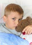 Garçon malade avec l'ours de nounours Image libre de droits