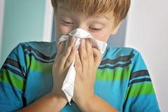 Garçon malade avec le nez de soufflement de grippe à la maison photo libre de droits