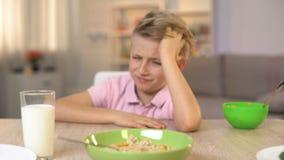 Garçon malheureux regardant la farine d'avoine avec dégoût, nourriture peu appétissante, petit déjeuner sain banque de vidéos