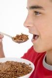 Garçon mangeant de la céréale de feuilleté de chocolat Image stock