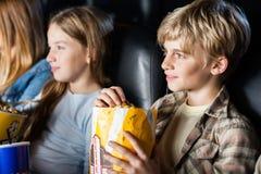 Garçon mangeant du maïs éclaté tout en observant le film avec image libre de droits
