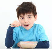 Garçon mangeant la farine d'avoine photos stock