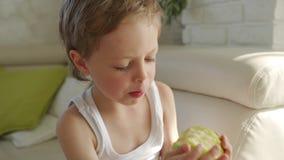 garçon 6 an mangeant la pomme verte et essayer de retirer des dents de lait banque de vidéos