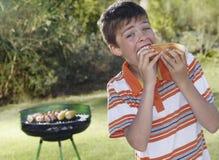 Garçon mangeant la saucisse de francfort avec le gril de barbecue à l'arrière-plan Image libre de droits