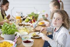 Garçon mangeant le dîner sain avec des amis à la maison Image stock